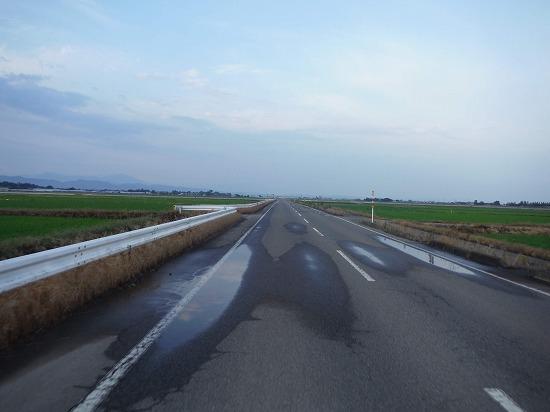 薄曇りの空の下まっすぐに延びる道